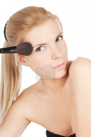 Beautiful young adult woman holds the make-up brush