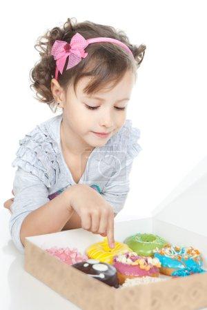 Photo pour Image de drôle de petite fille avec des beignets colorés sur fond blanc - image libre de droit