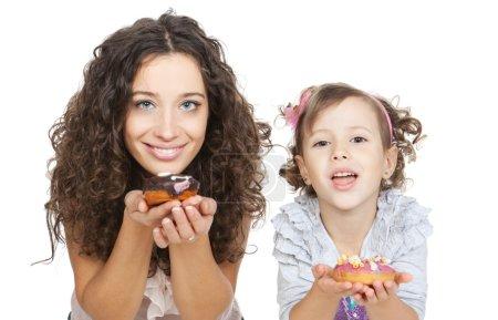 Photo pour Belle mère et petite fille mangeant des beignets colorés sur fond blanc - image libre de droit