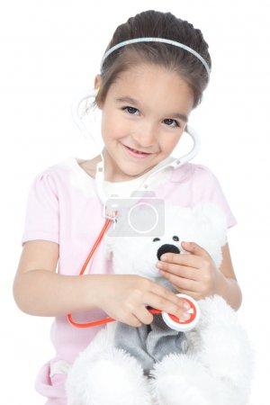 Photo pour Petite fille souriante jouant au docteur avec stéthoscope et ours en peluche, isolée sur du blanc - image libre de droit