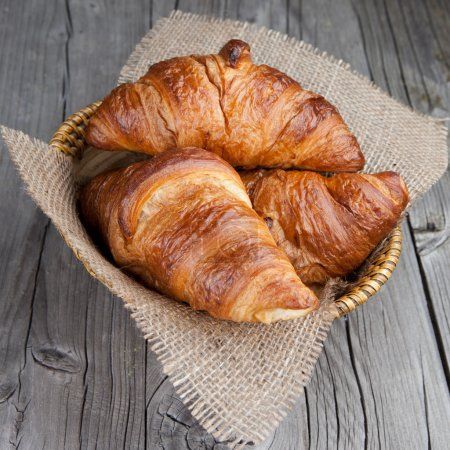 Photo for Crispy fresh croissants in a basket on a wooden table - Royalty Free Image