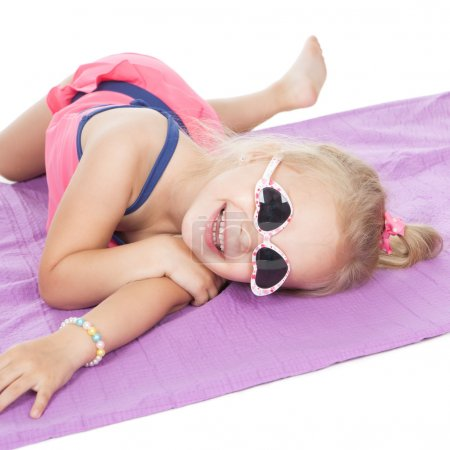 Photo for Cute smiling little girl in swimsuit and sunglasses lying on white background - Royalty Free Image
