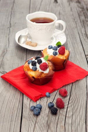 Photo for Fresh vanilla cupcakes with berries and cup of tea on old wooden background - Royalty Free Image