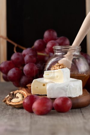 Photo for Baked Camembert cheese with honey, nuts and grapes - Royalty Free Image