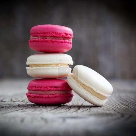 Photo for A stack of colorful French macarons on a dark rustic wooden background, selective focus - Royalty Free Image