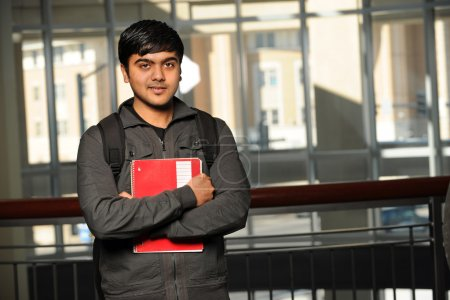 Photo for Portrait of young Indian student with school backpack holding notebook inside school building - Royalty Free Image