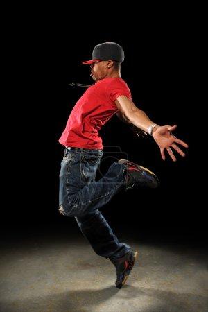 Photo pour Danseur de hip hop africain américain effectuant sur fond sombre avec le projecteur - image libre de droit