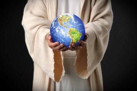 Photo pour Les mains de Jésus tenant le monde entre les mains sur un fond sombre - image libre de droit