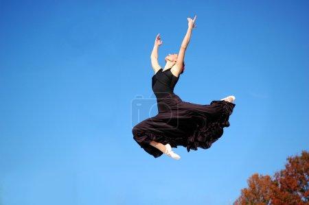 Photo pour Ballerine en tenue noire sautant à l'extérieur - image libre de droit