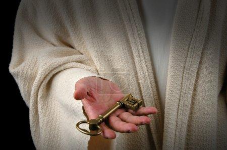 Photo pour Mains de Jésus offrant la clé du Royaume des Cieux - image libre de droit