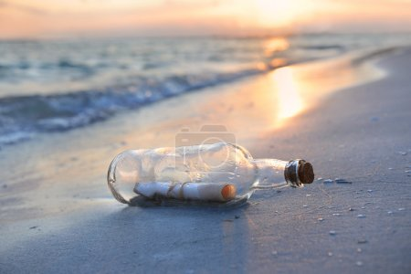 Photo for Message in a bottle resting on shore during sunset - Royalty Free Image