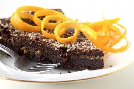 Photo pour Gâteau au chocolat avec une couche orange sur plaque blanche décoré de zestes d'orange. - image libre de droit