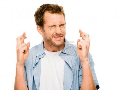 Photo pour Jeune homme faisant souhait doigts croisés - image libre de droit