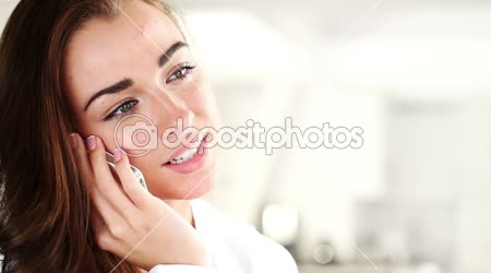 Joyful young woman talking on mobile phone at home