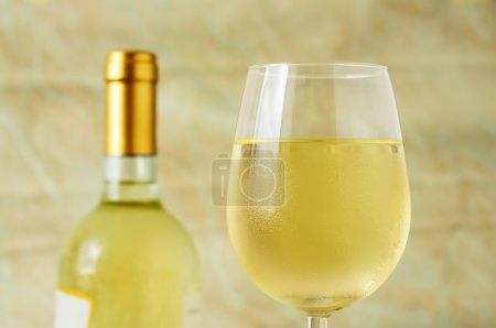 Glass and bottle of fine italian white wine, closeup