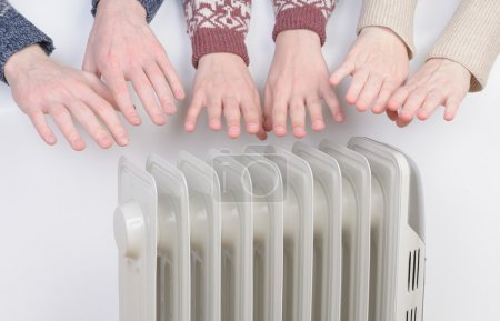 Family warming up hands over electric heater