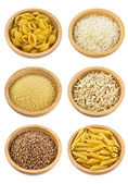 Different types of grains and pasta uncooked in wooden bowls