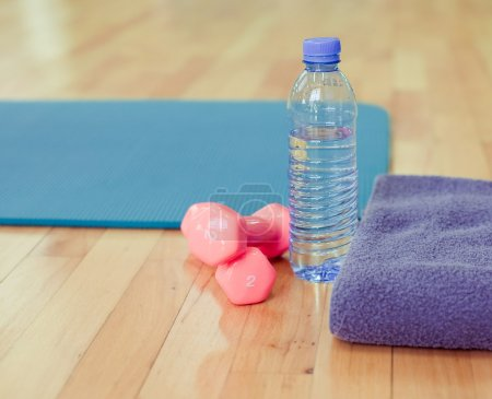 Bottle of water, sports towel and exercise equipment