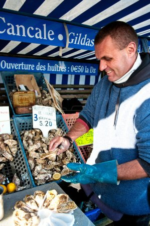 Oysterman opening oysters at market of Cancale, France