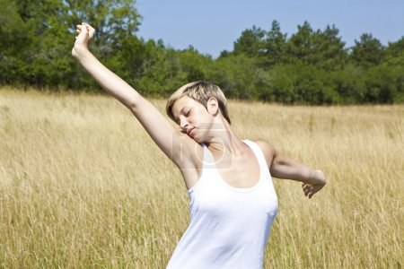 Photo for Young girl enjoying freedom in a field - Royalty Free Image