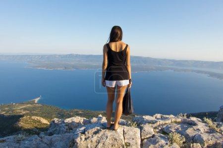 Photo pour Jeune femme à la recherche de panorama sur le plus haut sommet de brac, vue imprenable - image libre de droit