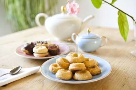 plates of pastries and biscuits and tea pot on wooden table
