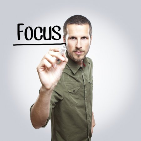 Photo for Young casual man writing FOCUS on glass board with marker - Royalty Free Image