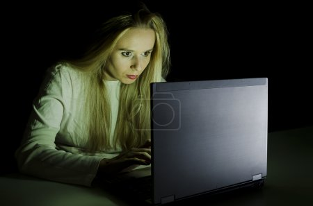 Woman working on a computer by night horizontal