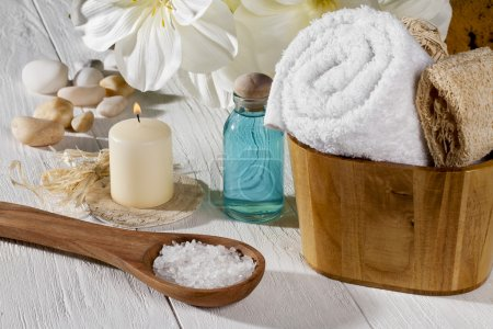 Photo for A set of spa products with spa salt on a spoon, towel, oil and a lighted candle on a wooden table - Royalty Free Image