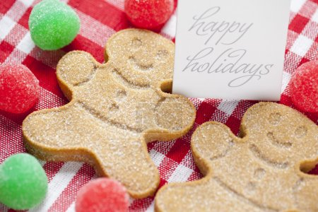 Photo for Close-up cropped image of gingerbread candies with happy holidays tag over red checked napkin. - Royalty Free Image