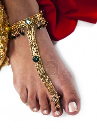 Photo pour Image en gros plan d'une jambe de femme portant un bracelet de cheville en or sur fond blanc. Modèle : Saudia Rakeel Cheveux, MUA et Sylist - image libre de droit