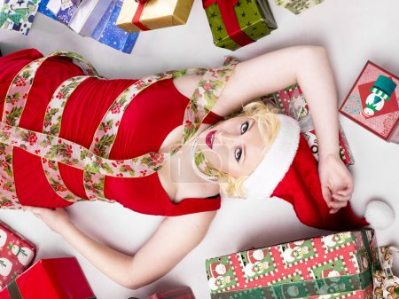 beautiful woman lying on back with gifts on the side