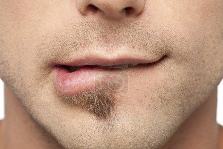 Photo pour Gros plan image de mâle mordant ses lèvres - image libre de droit