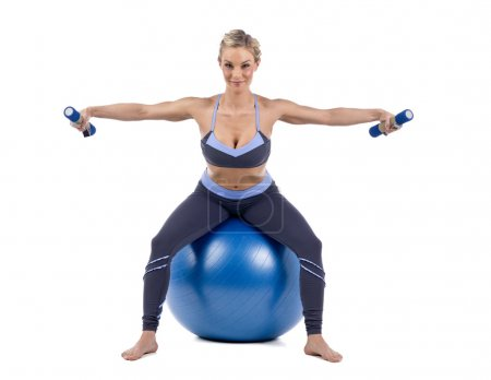 Photo for Young woman sitting on fitness ball and lifting dumbbells on white background - Royalty Free Image