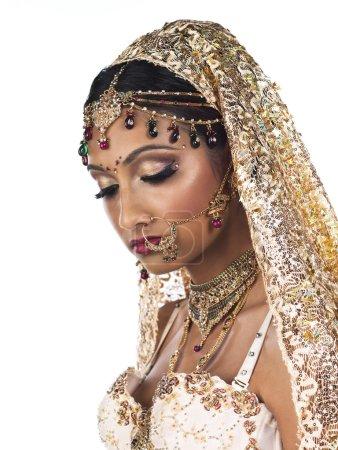 Photo pour Close-up vue latérale d'une séduisante jeune femme portant le costume de mariée et de bijoux élégants sur fond blanc Uni - image libre de droit