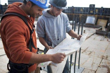 Photo pour L'équipe de construction discute du plan directeur - image libre de droit