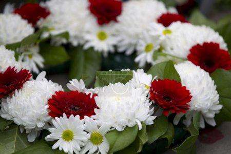 Photo pour Gros plan de la Couronne de fleurs rouges et blanches au Mémorial de guerre. - image libre de droit