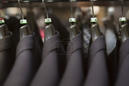 Photo for Close-up of business suits hanging in clothing store. - Royalty Free Image