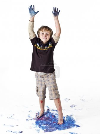 portrait of a boy making footprint on paper and hands raised