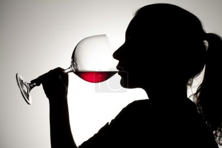 Photo for Silhouette shot of a female drinking red wine. - Royalty Free Image