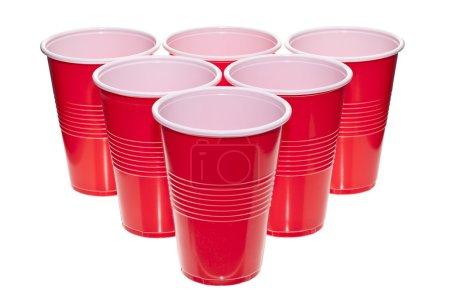 Photo pour Une pile de tasses en plastique rouges, disposés en une surface blanche - image libre de droit