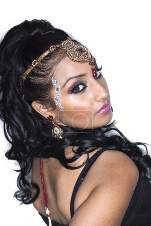An indian woman wearing traditional jewelry on white