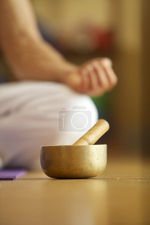 Photo for Singing Bowl in front of Man performing Yoga - Royalty Free Image