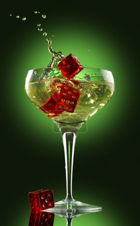 Champagne glass and dice over green background