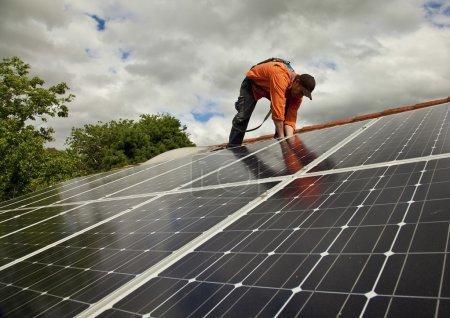 Foto de Electricista comprueba en la instalación de paneles solares en el techo de casa - Imagen libre de derechos