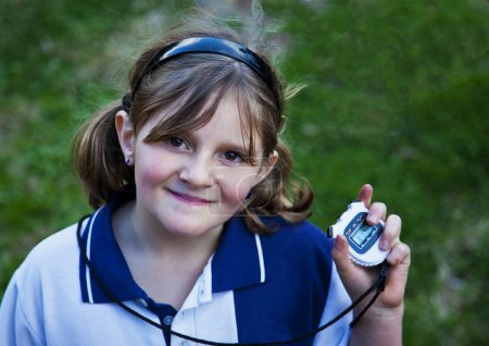 Happy young girl with stop watch at school sports day