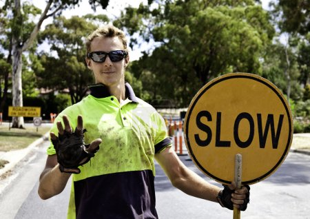 Photo for Roadworker controls traffic flow - Royalty Free Image