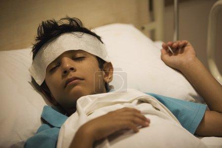 Boy with cloth on forehead