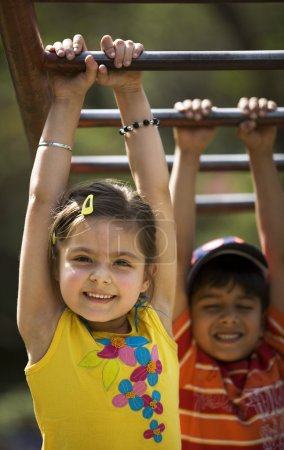 Children hanging on monkey bars