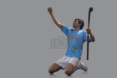 hockey player with stick celebrating success
